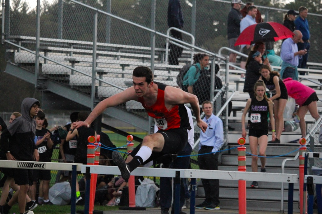 Junior+Nathan+Weinstein-Molloy+races+to+beat+his+opponents+in+the+400m+hurdles+while+the+rain+comes+down+around+him.+