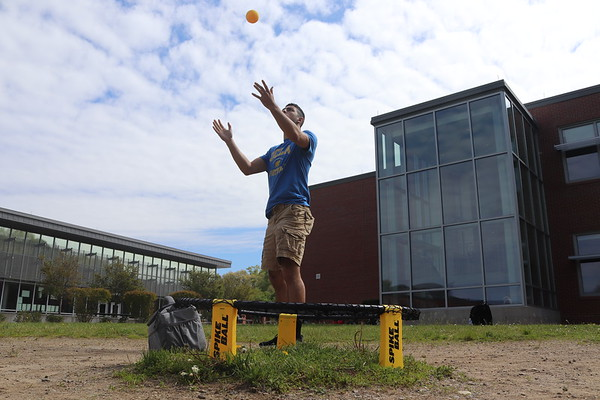 Junior Marcos Pereira serves the ball in a game of spikeball during a free. Alongside three other underclassmen, Pereira spent his free outside on the spikeball court.