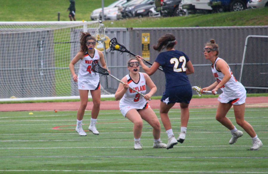 Junior+Erin+Greenberg+lunges+in+front+of+an+offensive+player+to+defend+their+goal.+