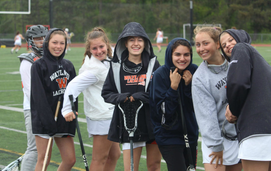 Freshmen Julia Wegerbauer, Sophie Ellenbogen, Emily Staiti, junior Christina Taxiarchis and sophomore Marley Miller pose for a photo on the sidelines.