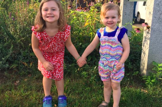 Ellie (left) and Annie Levine  (right) stand together holding hands smiling for a photo. When Ellie was diagnosed with leukemia in March, her family's life was changed forever.