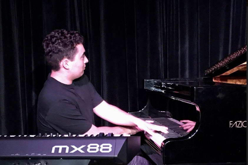 """Junior Lucas Alvarado plays the piano at a gig. Alvarado has been playing and performing music for most of his life. """"It's basically been my entire life, Alvarado said. That's basically my first memory. I remember waiting for my piano teacher to come over for the first time, and that is my most vivid memory from when I was three."""