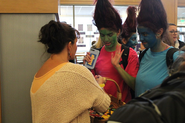Senior trolls Christina Taxiarchis and Fatma Sayeh receive candy during trick-or-treating from wellness teacher Rachel Hanks.
