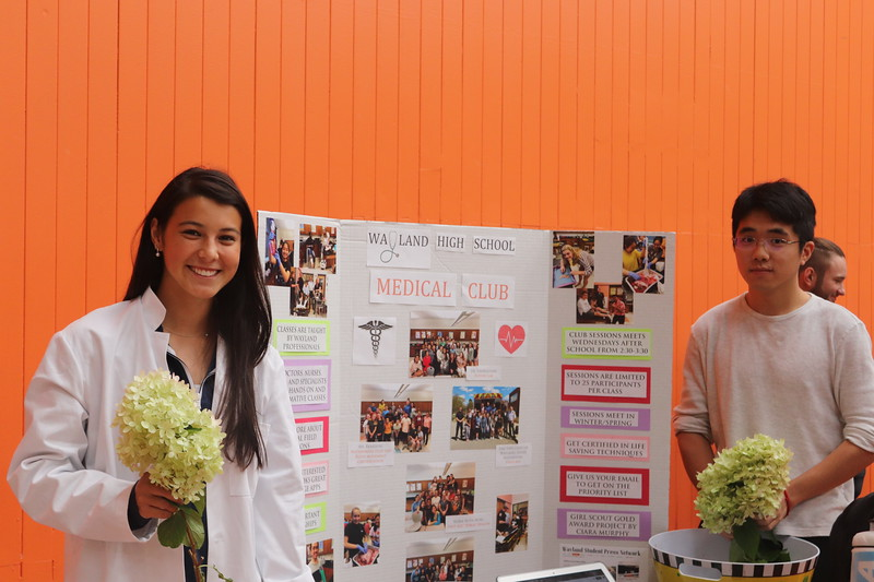Senior Ciara Murphy and junior David Feng are dressed in white lab coats as they stand in front of their Medical Club poster encouraging kids to sign up.