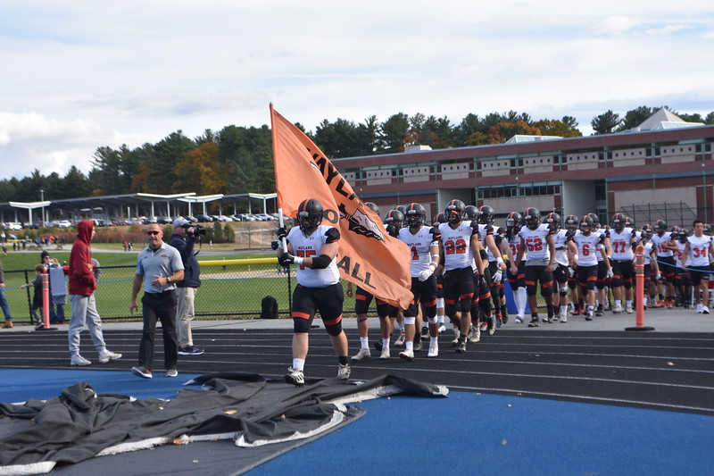 Senior Philip Koechling carries the Warrior flag and leads the team out onto the field.