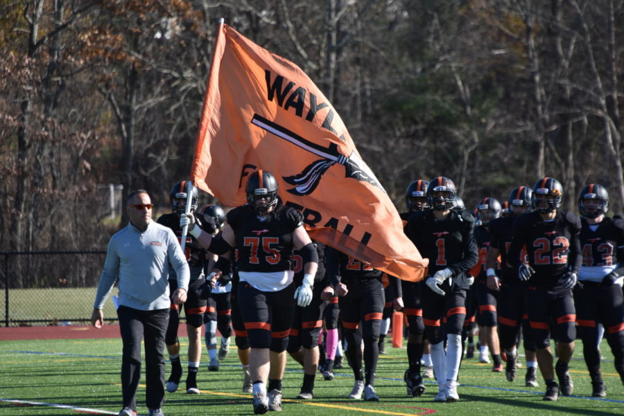 Senior Philip Koechling leads the varsity football team onto the field. Walking onto the turf with a flag is a tradition for the team.