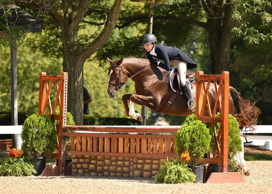 """Senior Savannah Sugar goes over a hurdle at a horse show. """"After all these competitions I have done I am ranked third nationally for the three-foot three inches Junior Hunter Division,"""" Sugar said."""