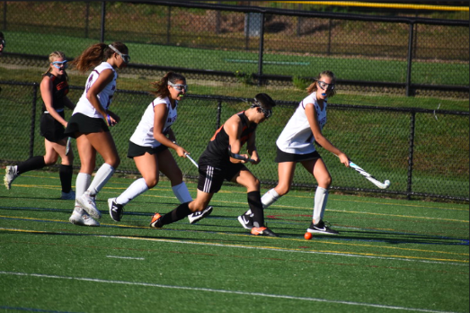 Forward senior Zeke Betancourt hits the ball away from Weston's defenders. The field hockey team has had a break through season as they enter the playoffs.