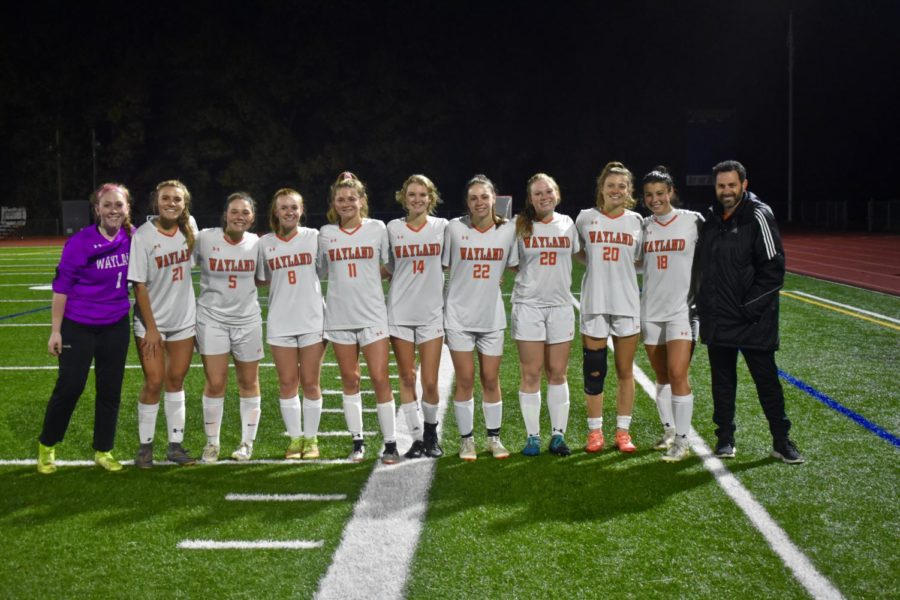 The team's seniors smile for a picture together. Although senior captain Carly Camphausen, a four year player, was injured the latter half of the season, she still able to be on the field during senior night to receive her flowers.