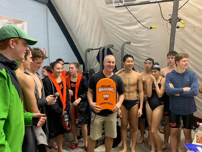 Wayland Warriors swim and dive head coach Mike Foley holds a kickboard after being awarded the 500th and 501st win of his career. Foley accepts this kickboard with the signatures of the athletes and coached who helped him achieve this goal.
