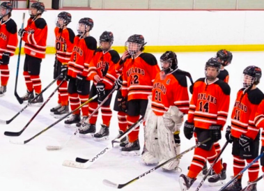 Last year's WHS boys hockey team lines up for the national anthem before a game. This year, the team is preparing for the season with two new goalies.