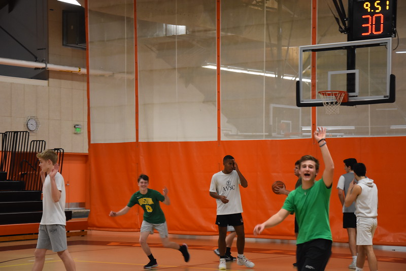 Goodfellow celebrates his basket by holding up a three indicating his shot was a three-pointer. The green team was very excited about Goodfellow's shot, closing the gap in the score.