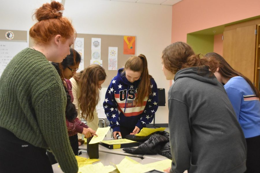 Freshmen Sadie Norgaard, Amelie Martin, Alex McQuilkin, Trisha  Raj, Grace Marto and Bryn Curtin work together as a team in room B136. They spread the clues out to look for any details they missed.