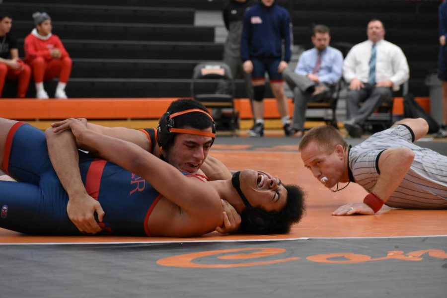 The referee counts back points as Pereira attempts to pin his opponent. The referee is using his second whistle of the day, having broken his first earlier due to exuberant whistling. Pereira, who wrestles at 182 pounds, won the match.