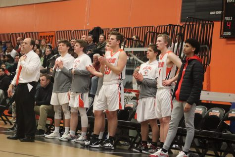 The boys varsity bench cheers while their teammates begin to take the lead. The team was down in the first quarter 3-14, but end up coming back, quickly taking and not letting up the lead.