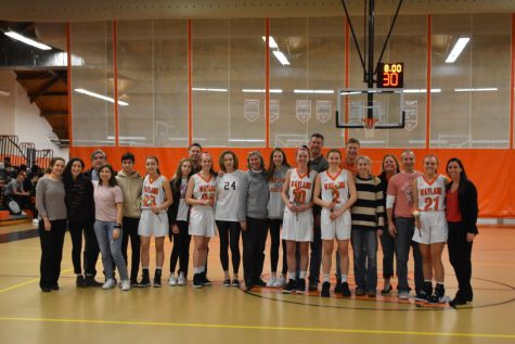 The senior players smile as they gather with their families and coach while taking a photo before the game.