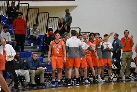 The team jumps to their feet and cheer as they score a basket, bringing the score closer. Throughout the season, the boys never failed to have enough energy from the bench.