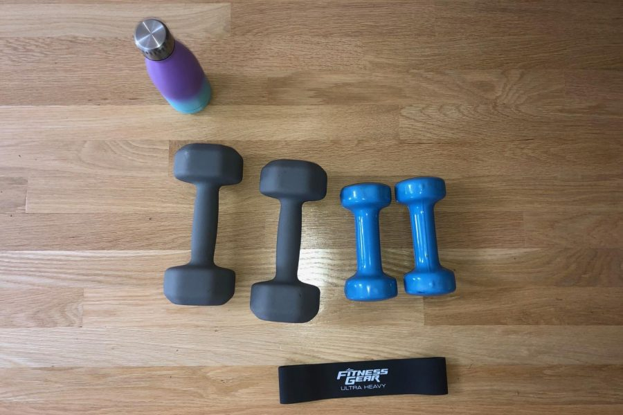 Pictured are a water bottle, dumbbells and a resistance band. Neither the weights nor the resistance band are required, but they are still great for many other workouts.