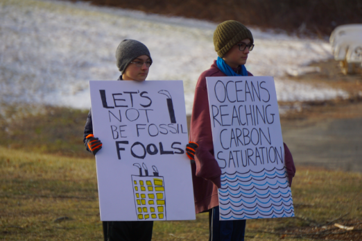 "Sixth-grade twins, Marley and Julian Eggers, hold signs at one of their daily climate strikes in front of WMS. The brothers began protesting in September as a way to call out inaction by adults on the climate crisis. ""There's a lot of harsh realities,"" M. Eggers said. ""When we look at adults, it's a little bit hard not to notice that they're not doing enough, or in general, not doing anything. They should be tackling this issue."""