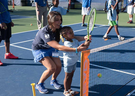 A volunteer who works with the organization ACEing Autism helps a little girl hold a tennis racket. ACEing Autism is an organization that was started to help kids with autism learn how to play tennis and there are many volunteers that help out.