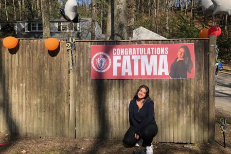 """Senior Fatma Sayeh poses in front of her decorations, prior to her celebration. """"In addition to seeing my friends drive by, I loved seeing so many faces that I hadn"""