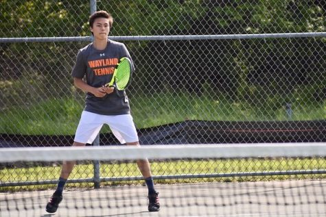 Boys varsity Junior tennis player Noah Lee stands ready in a singles match during last year