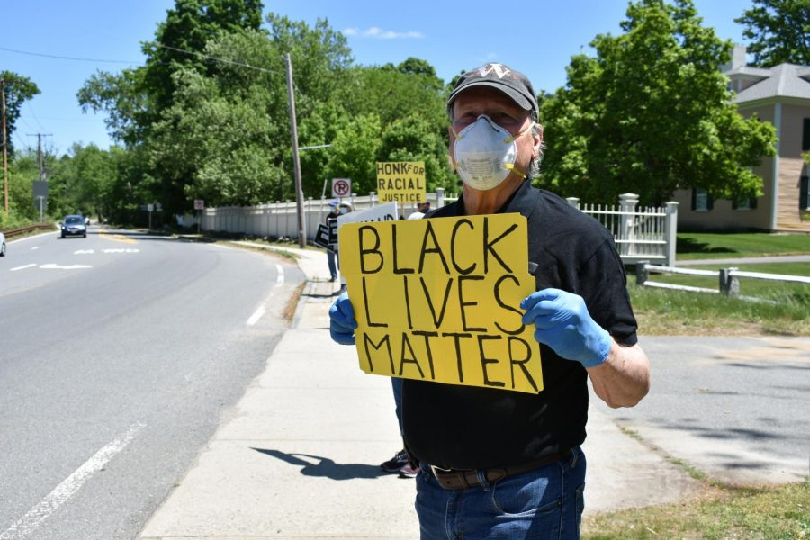 Malcolm Astley holds a 'Black Lives Matters' sign in front of the First Parish Wayland.