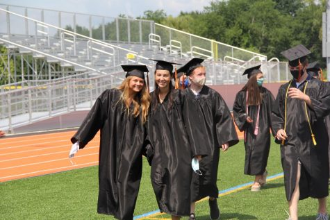 Seniors Caroline Lampert and Ciara Murphy pose while leaving their graduation.