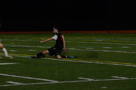 Senior defender Eric Zhang lunges for the ball, as he tries to prevent a scoring chance for Weston. Zhang was pivotal in limiting Weston
