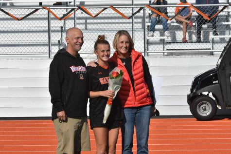 "Senior captain Abby Gavron poses with her parents as she is celebrated for an extraordinary four years on the team. ""[My favorite part of senior night] was seeing all the decorations and posters the juniors made. It meant so much that they did that,"" Gavron said. ""Also, beating Weston was a great feeling, especially on senior night."""