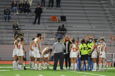 """As time runs out of the first half, coaches and teammates gather to discuss further plays in the next half. """"My favorite part of the season so far is coming together as a team,"""" O"""