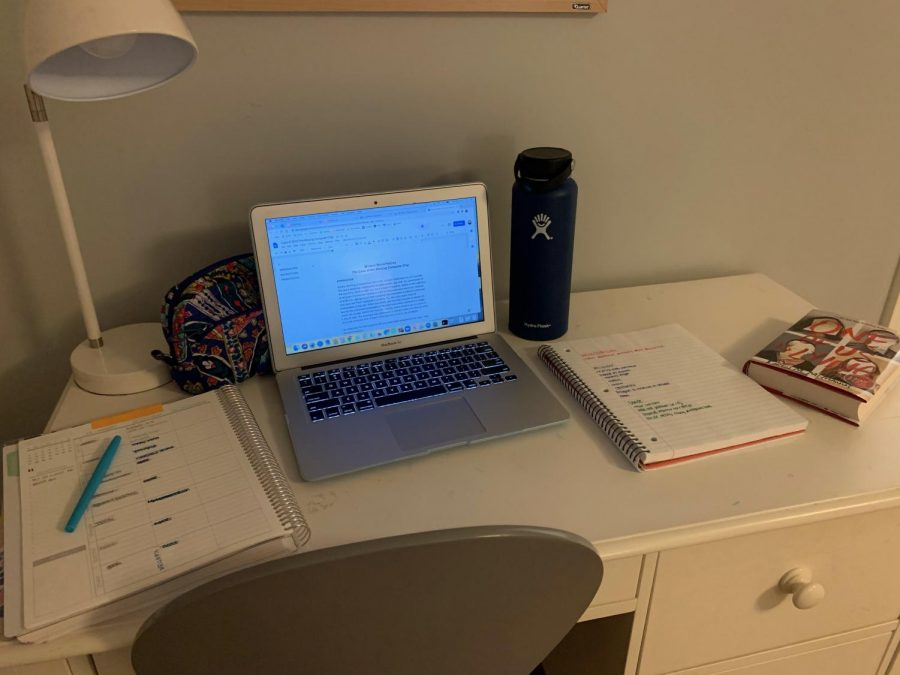 "Freshman Maggie Melander lays out her work as she gets ready for a long day of school online. Starting out school online is one of the first steps into helping students transition back into in-person school. ""[This] is what has to happen in order for us to go back "" freshman Maggie Melander said."