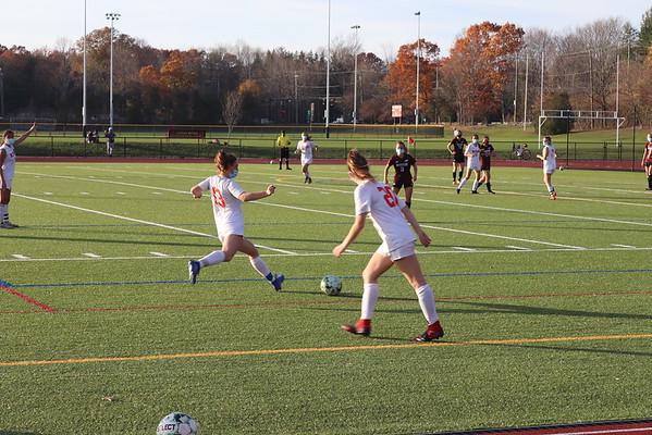 Junior Eliya Howard-Delman takes a kick as her teammates prepare to receive the ball.