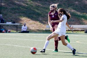 Senior captain Tali Wong on the Wayland girls varsity soccer team looks to play a ball to the forwards to create a scoring opportunity.