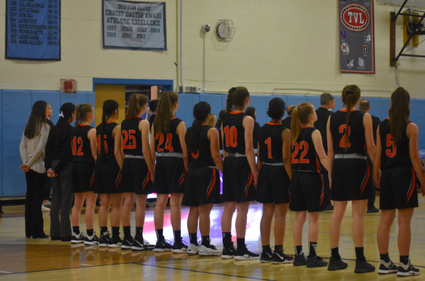 The girls varsity basketball team lines up prior to a playoff game last winter. Although the season is scheduled to tip off in around a month, the team has not had any organized basketball activity together.