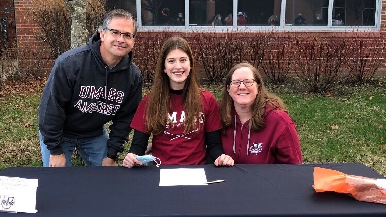 Foreman smiles with her parents on the Senior Signing Day, an annual event where recruited college athletes officially sign papers announcing their commitment to their college.