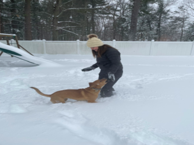 Eighth-grader Emma Alongi runs around in the snow with her dog during wellness class. Middle schoolers were encouraged to go outside and enjoy the snow during their online wellness class today.