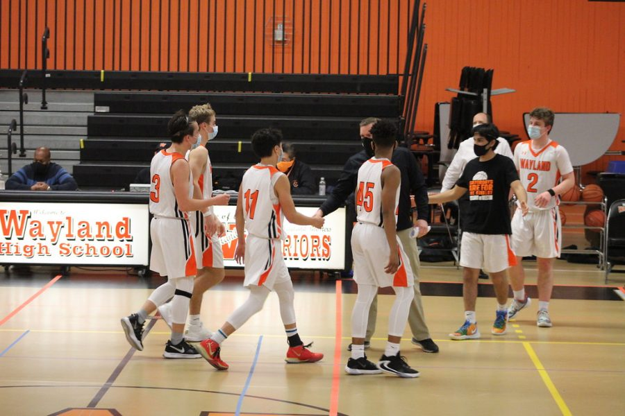 Players are greeted by their other teammates and coach as they walk off the court. The game consisted of frequent breaks for sanitizing and mask breaks.