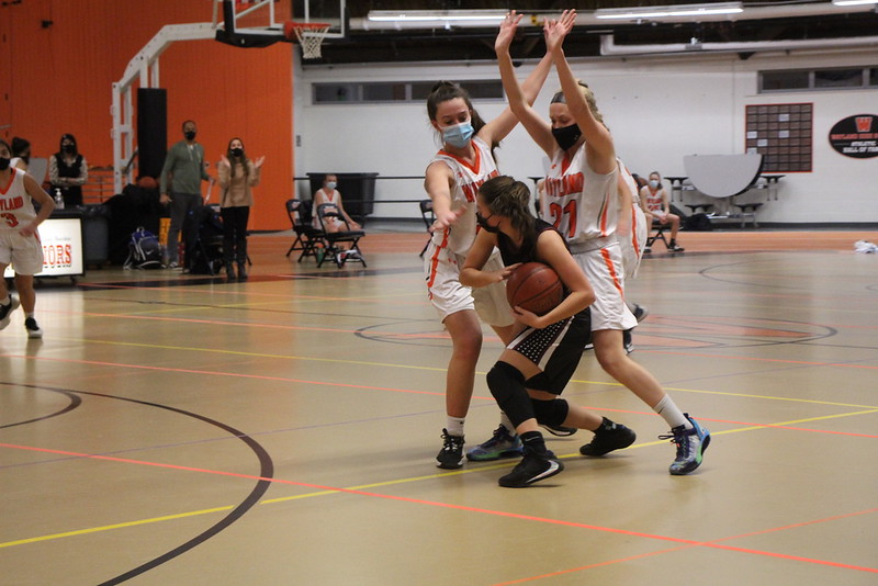 Junior captain Haley Melvin and freshman Ava Renneker raise their arms up high as they double-team a Weston player.