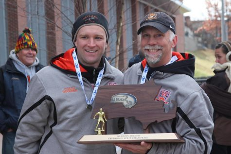 "Head coach of the Wayland varsity boys soccer team, David Gavron, holds the 2014 state championship trophy, alongside assistant coach Charles Goodhue. Gavron has been the head of the boys soccer program since 2008, and the program has won 3 state titles under his leadership. ""I"