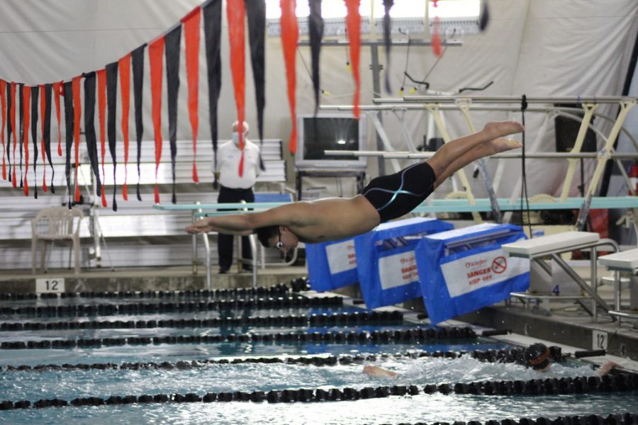 Senior Nate Cheribum dives into the water and continues his team's relay. The relays consisted of four swimmers, all swimming the same distance.