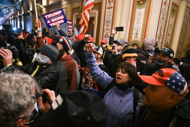 Natick resident Suzanne Ianni holds her hand up as she is inside the Capitol Building. On Jan. 6, 2021 Ianni participated in the mob alongside Trump supporters that rioted inside the Capitol Building.