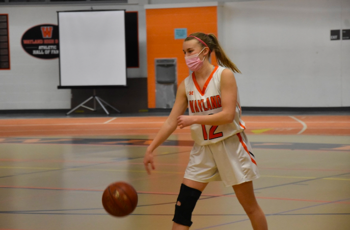 Senior varsity basketball captain Abby Gavron dribbles the ball on her senior night before being subbed out due to her torn ACL. Her injury requires surgery and a 6-9 month recovery with no contact sports.