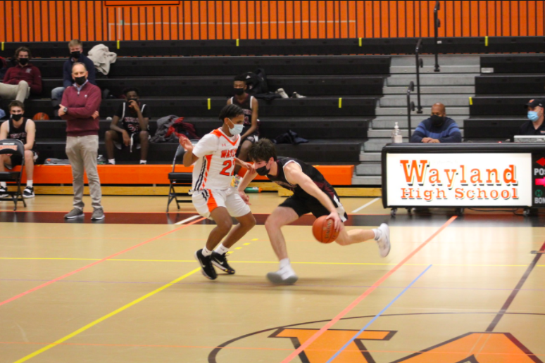 """Senior Dahlak Amanuel defends a Weston player as he dribbles the ball up the court. Despite the circumstances, the Wayland boys basketball team was able to rise above and have great success this season. """"I'm really thankful that I was able to end my career on a high note playing at a high level,"""" Amanuel said."""