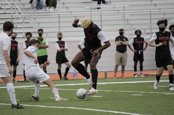 Junior Daniel Bede fights for control of the ball after a tackle from the opposing team. Bede is one of many athletes in the class of '22 that is trying to dodge COVID-19's obstacles as he looks to get recruited.