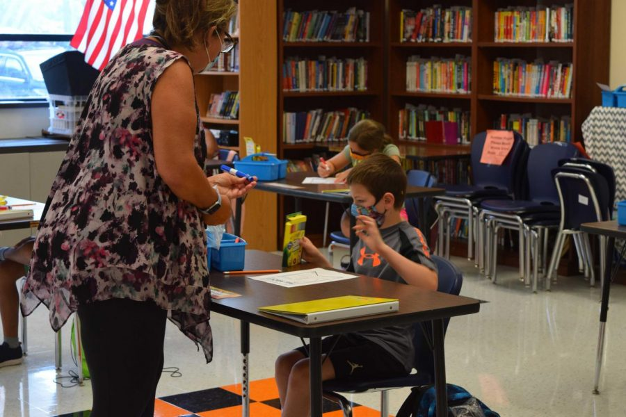 An elementary teacher assists a student with his work. The School Committee voted almost unanimously for elementary students to return to school all in person, five days a week starting April 5.
