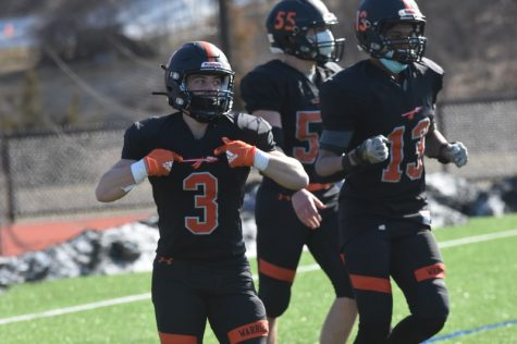 "In celebration of the touchdown ran by junior running back Shayne Sutton, senior Dylan Derubeis flashes his Warrior spear. For the next fall football season, the team will be receiving new and improved jerseys, so the players cherish the last moments in this iconic black and orange attire. ""Next year we have been informed that the spear will not appear on the new home black jerseys as it is"