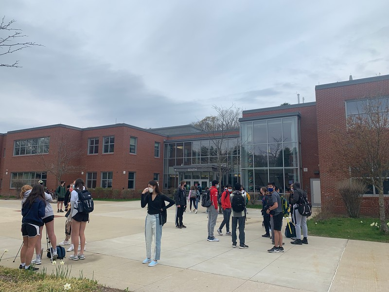 Wayland High School students gather in small groups outside of school before classes start. Many students are enthusiastic about returning all-in and are excited to return to normalcy.