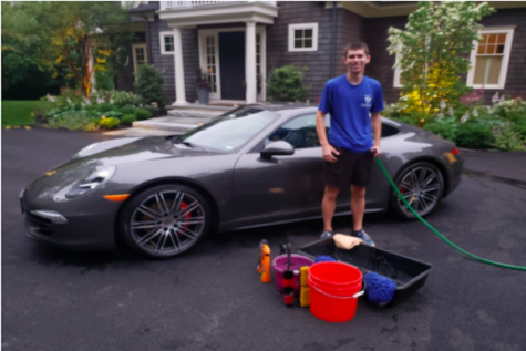 """Senior Zach Marto smiles near one of his customers cars. Since he started Marto's Mobile Car Care, his business services have expanded greatly. """"It started out strictly as only washing cars and it was just me at the beginning,"""" Marto said. """"It eventually evolved into where it is today where we do detailing services, waxing services, and we go on the inside of the cars."""
