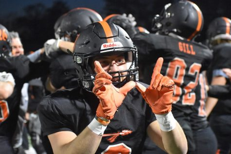As his team behind him gathers in celebration, screaming and hugging, senior Dylan Derubeis makes a W with his hands, symbolizing their victory over Holliston. Derubeis retires his high school football career with a huge win under his belt.